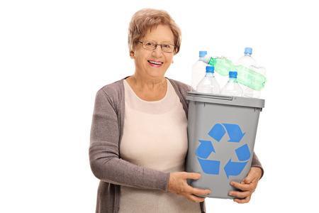 reciclable: Mujer madura feliz celebración de una papelera de reciclaje llena de botellas de plástico aislado en el fondo blanco