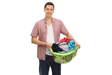 launder: Young man holding a laundry basket full of clothes isolated on white background