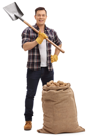 Full length portrait of a male agricultural worker posing with a shovel and a burlap sack filled with potatoes isolated on white background Stock Photo