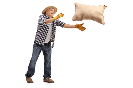 Full length portrait of a mature farmer throwing a burlap sack isolated on white background