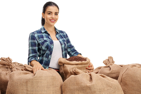 Female agricultural worker posing with burlap sacks filled with coffee beans isolated on white background Stock Photo