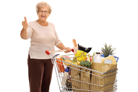 Cheerful mature lady with a shopping cart full of groceries giving a thumb up isolated on white background