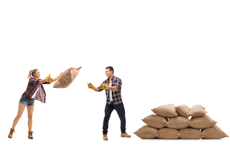 sackful: Female farmer throwing a burlap sack at a male farmer standing next to a pile of burlap sacks isolated on white background Stock Photo