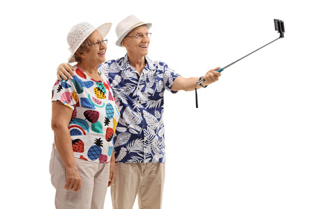 Mature tourists taking a selfie with a stick isolated on white background Stock Photo