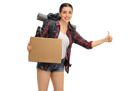 Female hiker hitchhiking and holding a blank cardboard sign isolated on white background