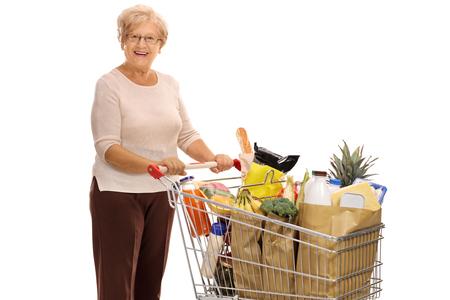 Vrolijke rijpe dame met een winkelwagentje vol met boodschappen op een witte achtergrond