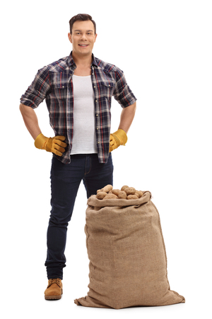 Full length portrait of young farmer standing behind a burlap sack filled with potatoes isolated on white background