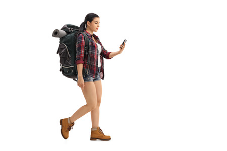 Full length profile shot of a female hiker walking and looking at a cell phone isolated on white background