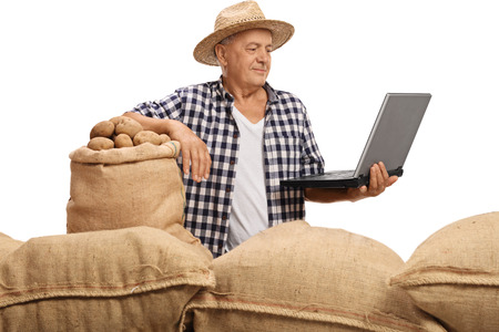 Elderly farmer with burlap sacks filled with potatoes looking at a laptop isolated on white background Stock Photo