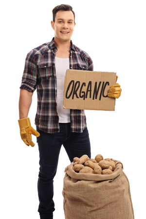 sackful: Young farmer with a burlap sack filled with potatoes and a cardboard sign that says organic isolated on white background