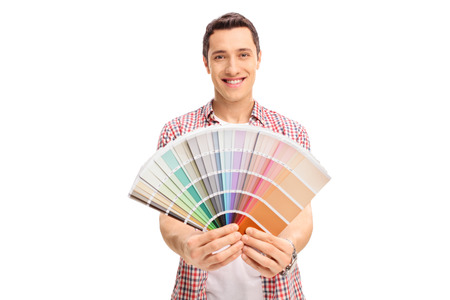 Happy young man holding a color swatch isolated on white background Stock Photo