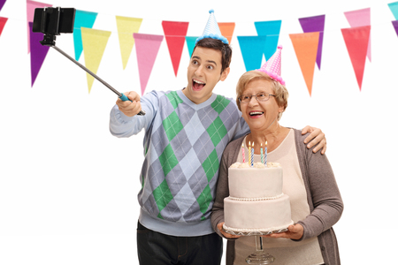 Young man and a mature woman with party hats and a birthday cake taking a selfie with a stick isolated on white background Stock Photo