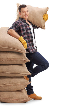 sackful: Agricultural worker with a burlap sack on his shoulder leaning on a stack of burlap sacks isolated on white background
