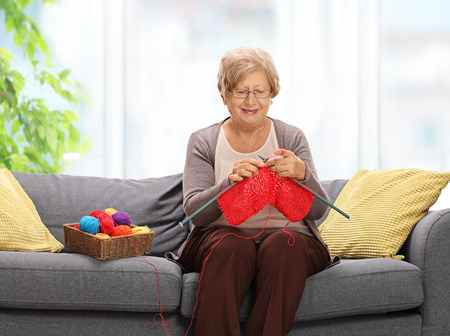Elderly woman sitting on a sofa and knitting