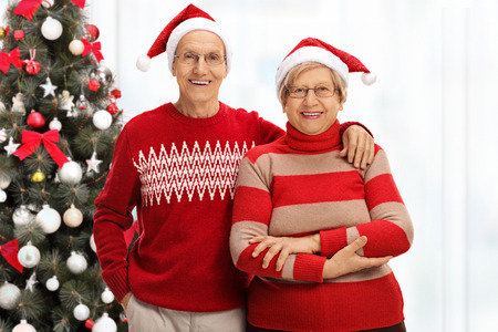 Cheerful senior couple with Santa hats in front of a Christmas tree