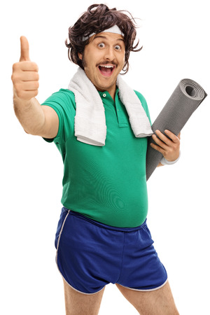 Retro sportsman holding an exercising mat and giving a thumb up isolated on white background Stock Photo