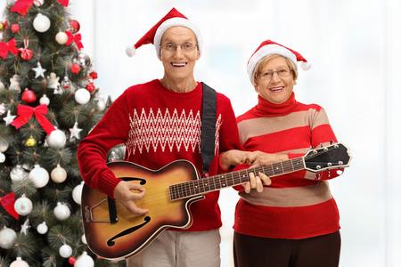ancianos felices: Personas de edad feliz jugando una guitarra en frente de un árbol de Navidad Foto de archivo