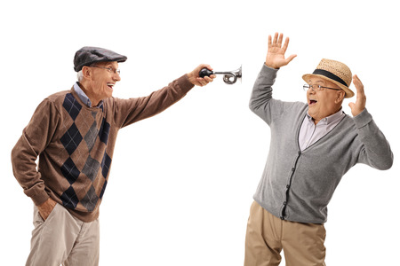 honking: Senior honking a horn and scaring another senior isolated on white background