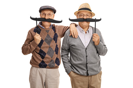 Seniors posing with big fake moustaches isolated on white background