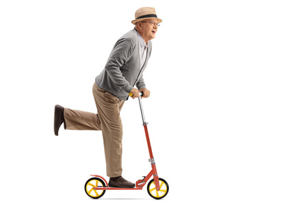 Full length profile shot of a joyful mature man riding a scooter isolated on white background Stock Photo