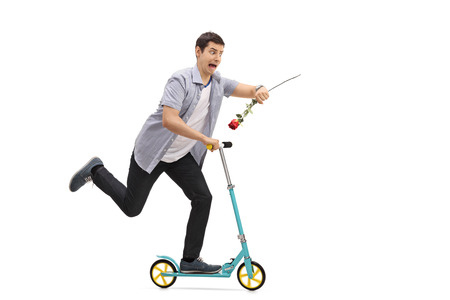 Full length portrait of a young man riding a scooter and being late isolated on white background Stock Photo