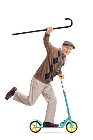 Full length portret van een vrolijke senior rijden op een scooter en met een wandelstok op een witte achtergrond Stockfoto