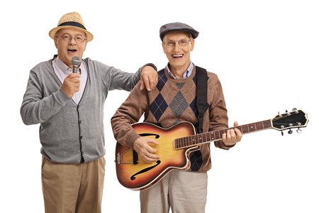 Elderly man singing on a microphone and another elderly man playing a guitar isolated on white background Stock Photo