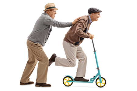 Full length profile shot of a mature man pushing another man on a scooter isolated on white background