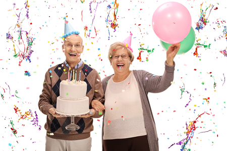 overjoyed: Overjoyed seniors celebrating a birthday with a cake and balloons isolated on white background Stock Photo