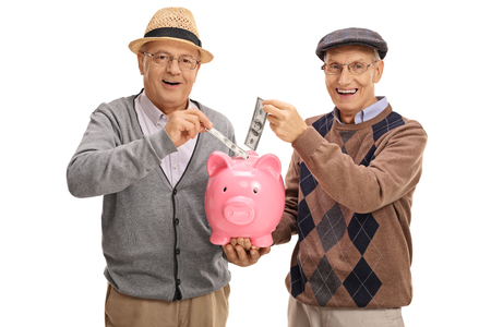piggy: Seniors putting money in a piggybank and looking at the camera isolated on white background