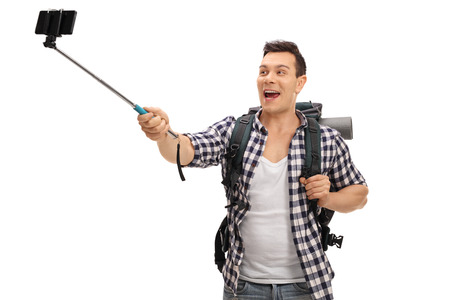 phone isolated: Young hiker taking a selfie with a stick isolated on white background