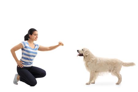 mujer arrodillada: Mujer joven que da una galleta a un perro aislado en el fondo blanco
