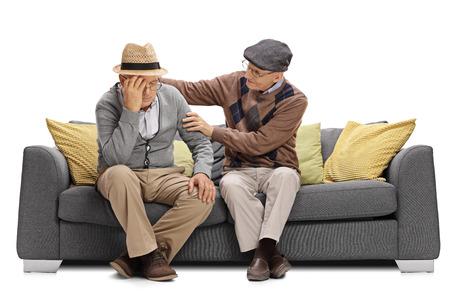 anciano sentado en un sofá y reconfortante otro hombre aislado en el fondo blanco
