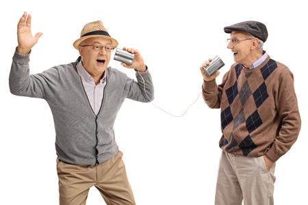 las personas mayores alegres contando chistes entre sí a través de un teléfono de lata aislado en el fondo blanco