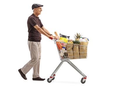 Full length profile shot of an elderly man pushing a shopping cart filled with groceries isolated on white background Stock Photo