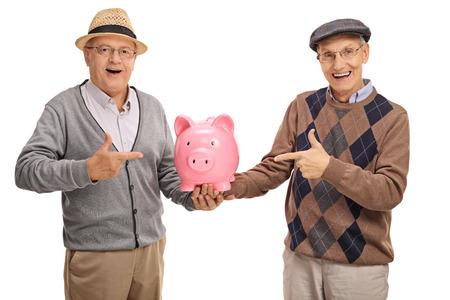 Happy seniors holding a piggybank and pointing isolated on white background Stock Photo
