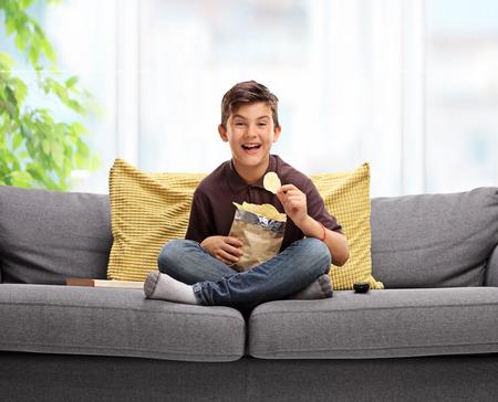Joyful bambino seduto su un divano e mangiare patatine fritte