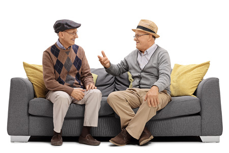 Two elderly men sitting on a sofa and talking isolated on white background Stok Fotoğraf
