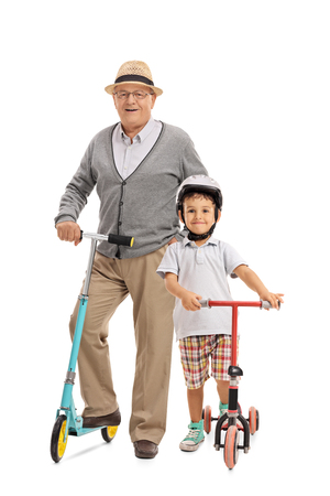 Full length portrait of an elderly man and a little boy with scooters isolated on white background Foto de archivo