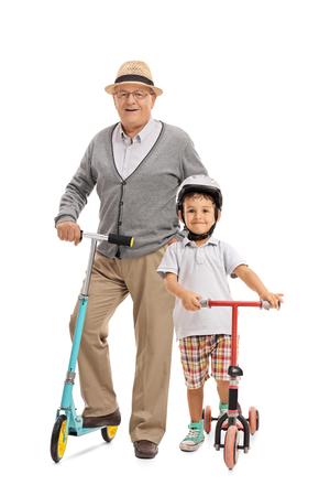 patada: Retrato de cuerpo entero de un anciano y un niño pequeño con los scooters aislado en el fondo blanco Foto de archivo