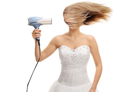 Bride soufflant ses cheveux avec un sèche-cheveux isolé sur fond blanc