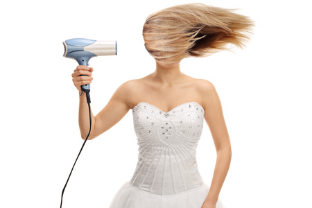 secador de pelo: Novia que sopla su pelo con un secador de pelo aislado en el fondo blanco