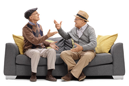 Two elderly men sitting on a sofa and arguing isolated on white background