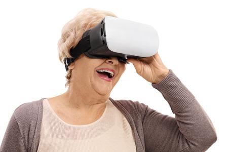 ancianos felices: Feliz anciana usando un dispositivo de realidad virtual aislado en el fondo blanco