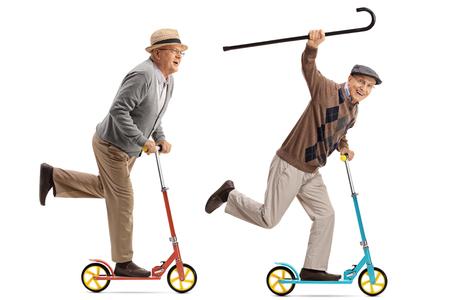 patada: Retrato de cuerpo entero de dos personas mayores que montan overjoyed scooters aislado en el fondo blanco Foto de archivo