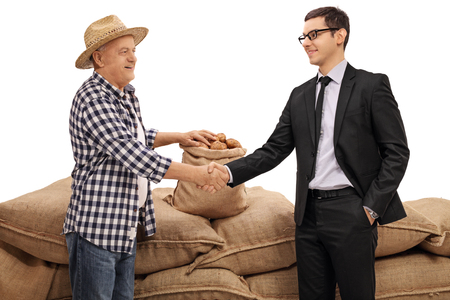 sackful: Farmer and a businessman shaking hands in front of a pile of burlap sacks filled with potatoes isolated on white background Stock Photo