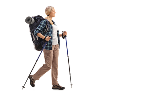 full shot: Full length profile shot of a woman with hiking equipment walking isolated on white background Stock Photo