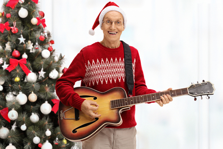 Happy senior playing an acoustic guitar in front of a christmas tree Stock Photo