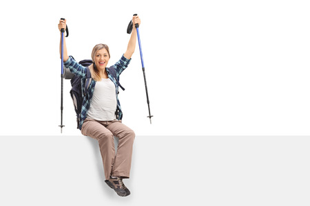 overjoyed: Overjoyed female hiker sitting on a panel isolated on white background