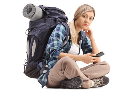 sitting on the ground: Worried female hiker holding a mobile phone and sitting on the ground isolated on white background
